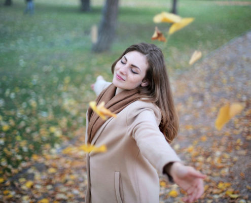 Woman standing outside with arms open, enjoying autumn leaves
